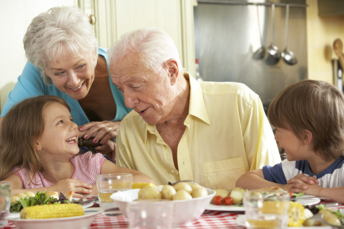 Grandparents,And,Grandchildren,Eating,Meal,Together,In,Kitchen